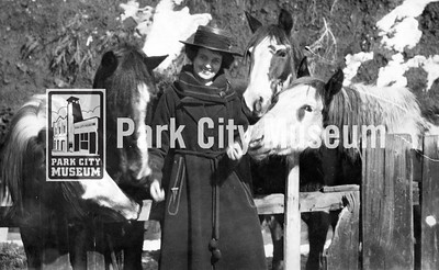 Carrie Hodgson with four of her paint horses, who are behind a wooden fence, nudging at her as if she has oats in her hand.  A smiling Mrs. Hodgson wears a long winter jacket and pork pie straw hat. circa 1890-1920. (Image: 2010-16-10, PCHS Photograph Collection)
