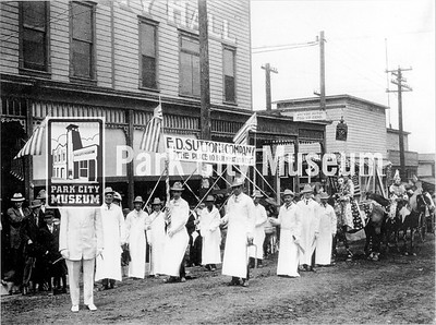 "E.D. Sutton & Company owner and employees wearing white with women in starred dresses on horseback ready for a parade. They hold a sign that reads: ""E.D. Sutton & Company 'The Place to buy what you eat.'"" circa unknown (Image: 2007-11-89B, Thomas F. Hansen Collection)"