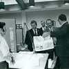 At left: Charlie Burton of the Instruction Materials Lab; Dr. Harlacher holding rendering
