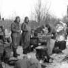 "Photo courtesy of Fred Korb<br /> Soldiers make and eat doughnuts in their ""outdoor bakery."""