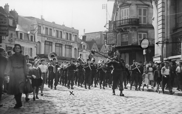 "Photo courtesy of Fred Korb<br /> Children and adults follow the U.S. Army Band as it marches down a street in a liberated French town on the way to Paris in 1944.  The ""x""shows trombone player Fred Korb on the front line.  The Army fielded about  500 bands during World War II to play at official events, medal presentations, march in victory parades and entertain the troops.."