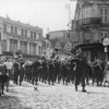 """Photo courtesy of Fred Korb<br /> Children and adults follow the U.S. Army Band as it marches down a street in a liberated French town on the way to Paris in 1944.  The """"x""""shows trombone player Fred Korb on the front line.  The Army fielded about  500 bands during World War II to play at official events, medal presentations, march in victory parades and entertain the troops.."""