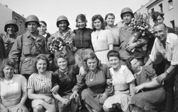 "Photo courtesy of Fred Korb<br /> American soldiers pose with Dutch residents after Allied forces liberated Holland in 1944.  They were given tulips. Korb, far right, titled this photo as ""Thanks for Freedom."""