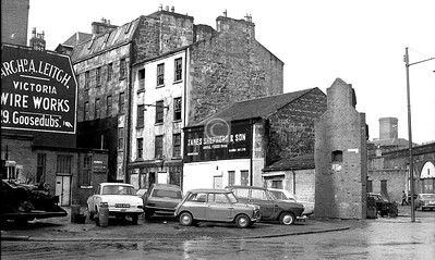 Goosedubbs at the Bridgegate.    This one took a bit of working out - it must have been taken from a few yards east of  Merchants Lane. Aird's Lane is entering Goosedubbs from the left, and on the far right is the end of Howard St.   The roof of, I think, the St Enoch locomotive shed shows above the railway arches.  The tall brick structure to the right of the cars has a hand-painted sign beneath the smoke-blackened aperture: NO NEED FOR ALARM - FISH BEING CURED. The Fish Market was of course just across the road, for another few years anyway.     March 1973