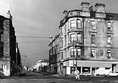 Looking down Stevenson St from Abercromby St.    Another interesting and impressive tenement block now demolished. Unusually, it had a stone balustrade and cast iron railing running the full length of the roof-line, guarding a rooftop drying area. The stone cartouche bears the city arms surrounded by the words 'Glasgow City Educational Endowments Board'.     February 1976