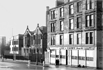 Greendyke St, west side at London Rd.   All gone now. The pleasant sort-of-baronial building seems to have been part of St Alphonsus' School, which had its main entrance in Charlotte St. Beyond, turning the corner, is the easternmost extension of the Camp Coffee works, to which the chimney belongs. This was started in 1891 by R Paterson & Son in the Adam house at the south end of the east side of Charlotte St, and was such a runaway success that the next 17 years were spent in what must have been an almost continuous process of rebuilding and extending. This corner building of 1908 was the last expansion, for the invention of instant coffee powder was not far in the future, and Camp's sales suffered. The brand has been sold on in modern times, and it is still in production (though not in Glasgow) and can be found in most supermarkets, albeit in the home baking aisle rather than with the tea and coffee.    January 1974