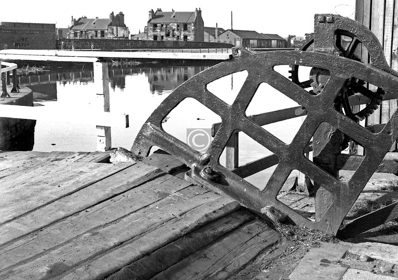 Applecross St bascule bridge.  The quadrant plate is still there (and the deck repaired), but the bridge is no longer hand-cranked. I think the tenements were in Oakbank Terrace but am prepared to be corrected on this.     March 1974