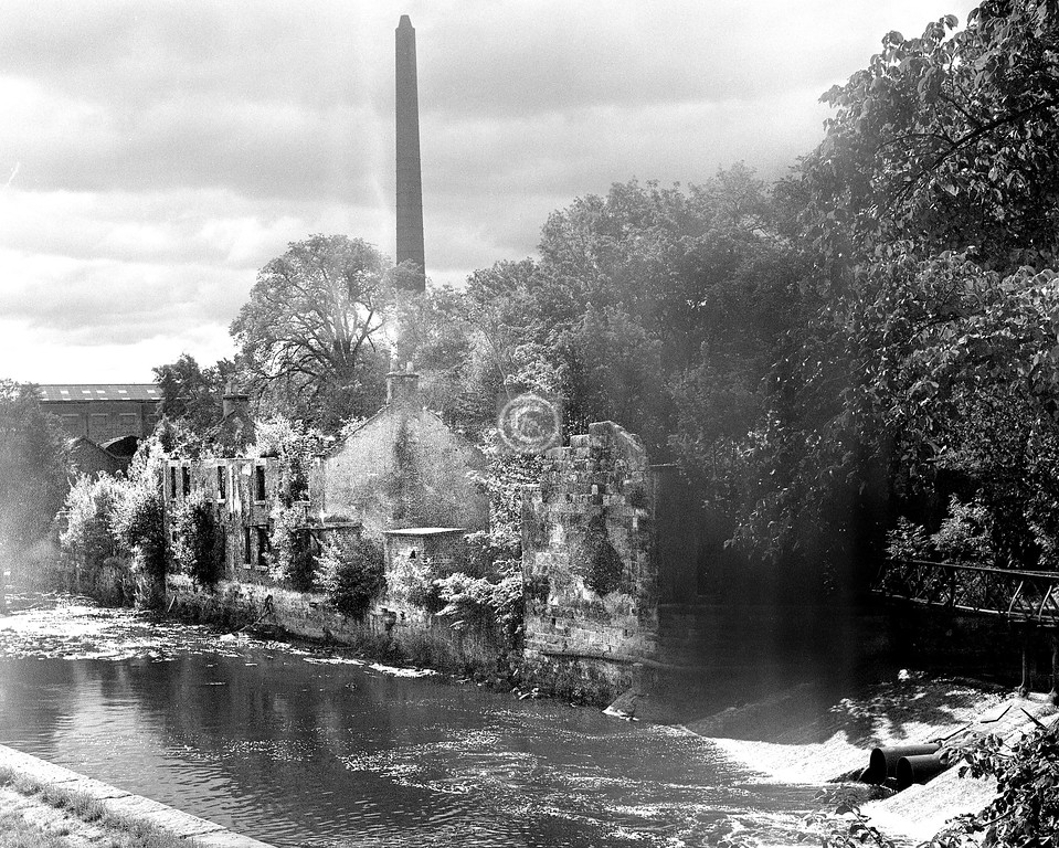 River Kelvin below the Kelvin Aqueduct.   The chimney and the further buildings were part of Kelvindale Paper Mill, the largest and last-surviving paper mill in the city. It closed around this time. The mill was founded in 1746 and was of course powered by water for many years, with the V-shaped weir on the right supplying the water to a large lade. The weir is still there, though not the iron footbridge which gave access to it for clearing debris from the corners. I have no confirmation that the riverside ruins were part of the mill complex but it seems very likely.  June 1976