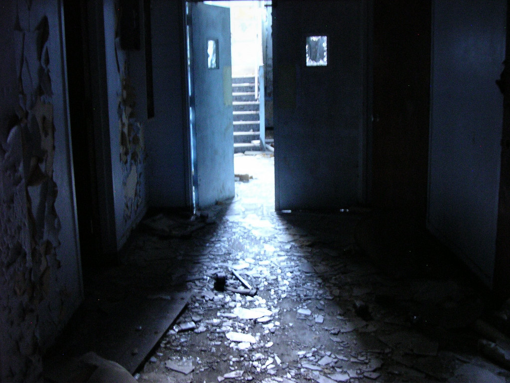 Corridor leading toward the front of the east main hospital bujilding on the first floor. The first-floor windows of all the buildings were boarded up when the complex closed; it's very dark in the areas where the boards have not been broken by vandals.<br /> <br /> 4-23-07