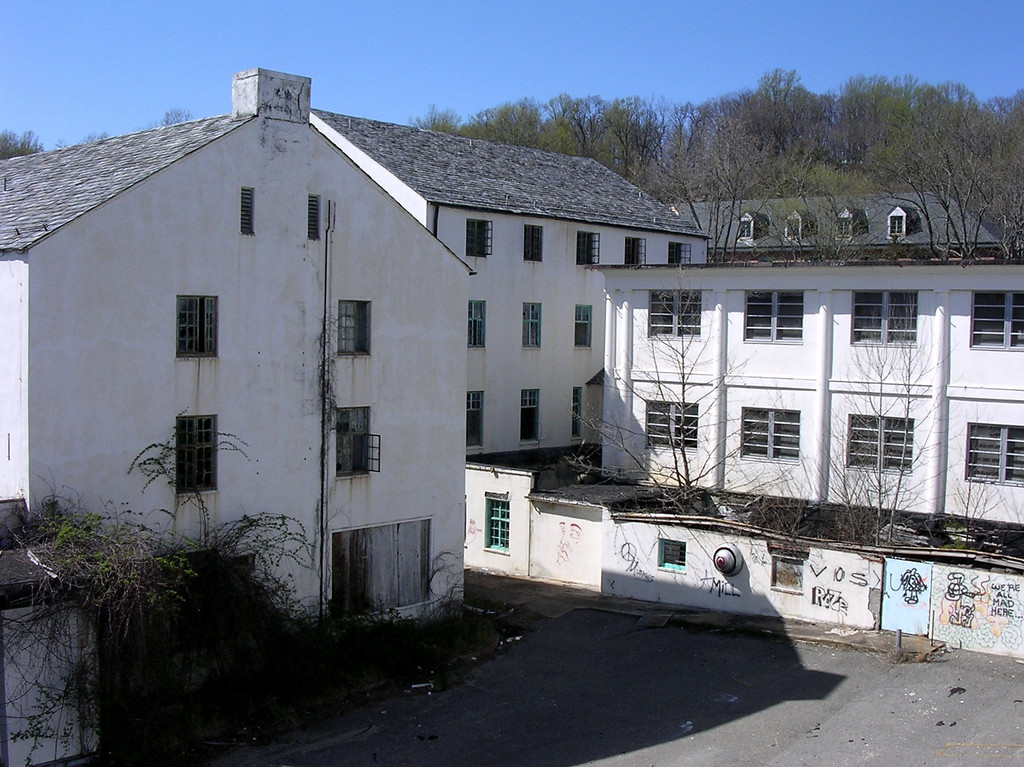 """The building in the background with the dormer windows is the """"new"""" administration building. The white building with the pitched roof directly across from the administration building is the back of the old main building seen in the first photo. The flat-roofed building at right is a wing of the east main hospital building. The kitchen is at the rear of the building on the left. <br /> <br /> 4-23-07"""