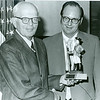 Board Chair Preston Corderman, Dr. Ervin Harlacher with original Jersey Blues figurine