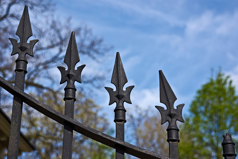 Since I can't believe people would install a bent cap on one of the posts in this wrought iron gate, I'm forced to conclude that something very heavy fell on it some time in the past.<br /> <br /> Main gate, Forest Hill Cemetery, Ann Arbor, Michigan<br /> April 21, 2012