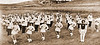 The Chadron State College marching band, led by drum majorette Doris Covie, posed for the photographer on the hill just east of Elliott Field.  The photo is circa 1960.