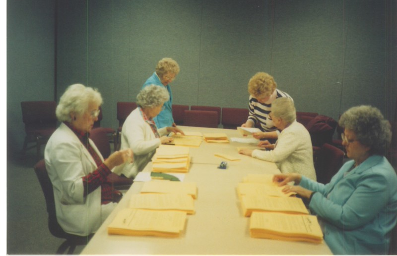 The ladies putting together the camper devotional books.