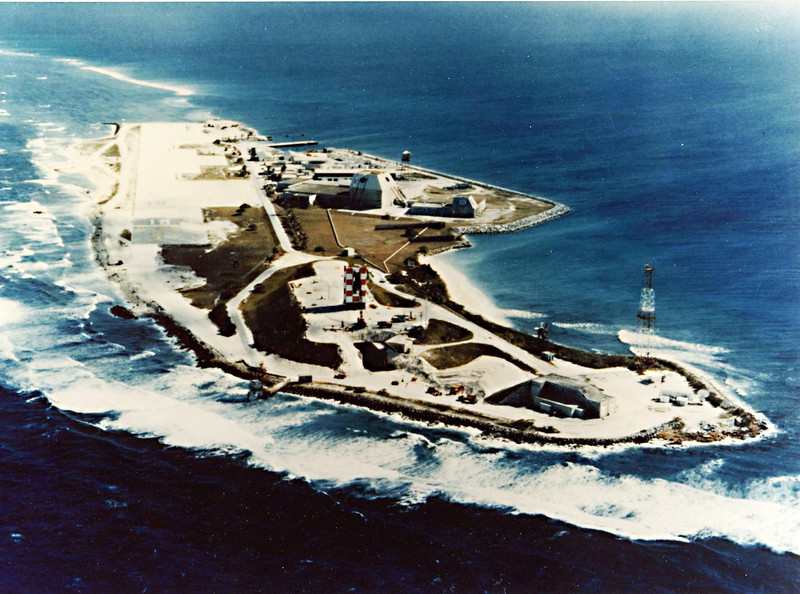 Meck Island, in the Kwajalein Atoll.  Minuteman warheads are routinely targeted into the lagoon of the atoll.  To test the capabilities of an Intercontinental Ballistic Missile Interceptor, Meck Island is ideal.  Note the red and white access stand in the center of the photo.  The launch point is just in front of the access stand, which has been rolled back.  When preparing the missile for flight, the access stand surrounds the missile.  This provides access for tanking propellants, preparing the sensor and electronics, etc.