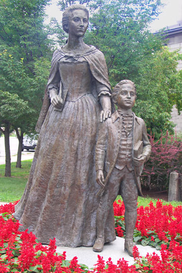 Statues of Abigail Adams and young John Quincy Adams near the Visitors Center. John Quincy Adams married a foreign-born American, Louisa Catherine Adams who was much beloved by the nation, and one of only three First Ladies for which the government declared a national day of mourning.