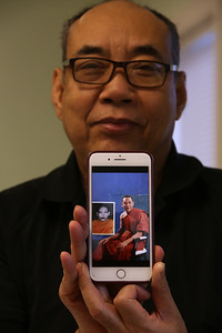 Survivor of the Khmer Rouge genocide in Cambodia,  Bunchhoeun Noun of Lowell, holds his phone showing photo (inset) of himself around age 22, in 1982, and another photo in Lowell in the mid-1990s. He was a Buddhist monk for about 10 years in Cambodia and 10 years in the U.S., which helped him deal with PTSD.  (SUN/Julia Malakie)