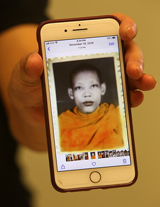 Survivor of the Khmer Rouge genocide in Cambodia,  Bunchhoeun Noun of Lowell, holds his phone showing photo of himself around age 22, in 1982. He was a Buddhist monk for about 10 years in Cambodia and 10 years in the U.S., which helped him deal with PTSD.  (SUN/Julia Malakie)