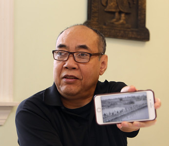 Survivor of the Khmer Rouge genocide in Cambodia,  Bunchhoeun Noun of Lowell, shows an online video of workers walking to rice paddies from a documentary about the genocide, as he talks about his experiences.  (SUN/Julia Malakie)