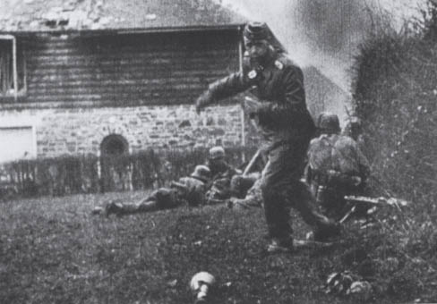 The half-timbered house between the police station and the church existed in 1944 and features prominently in film and photographs taken by German combat photographers during the battle for Stoumont. In this film, German paratroops are clearly seen setting up a machinegun in the then small field where the Gendarmerie now stands. In that same film, SS-Sturmbannführer Werner Poetschke can be seen turning around to pick up a discarded Panzerfaust anti-tank weapon.