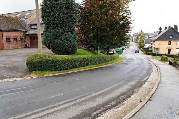 As the lead tank of Kampfgruppe Peiper began its descent into the village, Privates First Class Roger V. Foehringer and Alfred Goldstein of Service Battery 924th Field Artillery Battalion were walking up this hill carrying a box grenades. Upon reaching this bend in the road they came face to face with Peiper's lead tank. Dropping the grenades, they ran off to the front left as machine-gun bullets cracked all around them. Foehringer lay still as a second tank and a halftrack carrying ten or twelve SS-Panzergrenadiers sped down into the village following the first tank. From the garden/yard of the red brick house, just up from the bend, the two GIs could clearly see the vehicles moving down the hill past a stone house on the left (now demolished and replaced by a post-war structure on the same spot). Goldstein spotted two Service Battery cooks who were trying to load a bazooka from the wrong end. Rushing up to them he seized the weapon, loaded it and fired downhill at one of the tanks, the rocket detonating as it hit the side of the house. He and Foehringer then joined other Service Battery soldiers iriside the red brick house and for a short while they and other soldiers fired carbines and rifles at the German vehicles moving downhill into the village. Eventually, SS Panzergrenadiers captured the troublesome 'Amis' and after relieving them of watches etc. marched them south in the direction of Honsfeld.