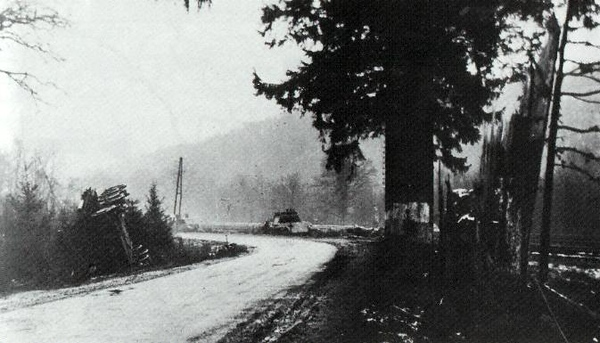 Around 14.30 on 19 December, the defending Americans knocked out Peiper's three lead tanks . The American View. One of the knocked out Panthers  is pushed to the side of the road and overturned another can be seen at the bend. The germans aproached towards the camera.