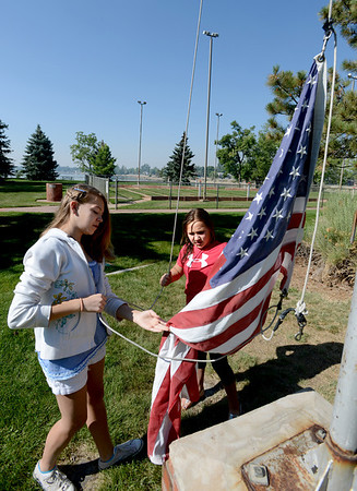 "Alexa Brolsma, left, and Amelia Dillow, raise the flag at Lone Tree School.<br /> For more photos and a video of the school, go to    <a href=""http://www.reporterherald.com"">http://www.reporterherald.com</a>.<br /> Cliff Grassmick / June 13, 2012"