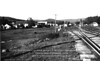 """Pettigrew, AR - mid / late 1930's, looking east along current route of AR Highway 16.<br /> <br /> This picture really tells the story of """"What happened after the boom-town days?"""" -- Twenty years earlier, the right-hand side of the image would have been stacked full of milled timber ready for transportation on the railway.  At the time of the photo, the depot freight yard, streets and storefronts are empty.  Grass is growing up along the tracks.  Unidentified boy standing at the siding switch (right-hand, mid-ground in image) looks east toward town and the Boston Mountains.<br /> <br /> Original negative in my collection, from my father's papers.  Shiloh Museum has a copy in their archives.<br /> <br /> Digital restoration (c) 2013 - Daniel P. Martin / ozarkimageworks.com"""