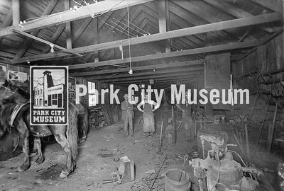 Interior of Berry Bros. blacksmith shop, once located at 6th and Main streets. Men identified as Bill Berry (middle) and Ed Berry (right) (Image: 1984-47-3, Wilma Larremore Collection)