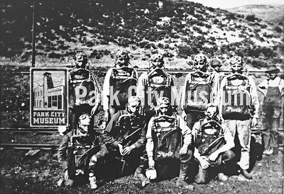 A mine safety and rescue team poses with their equipment, including masks and breathing apparatuses, ca.1915-1925 (Image: 1984-23-12, Bea Kummer Collection)