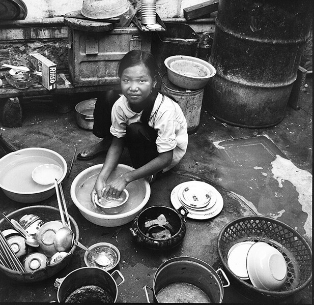 """See this Na Trang child's life all laid out for her. See the endless march of rice bowls, all to clean in Rinso Blue. Did the dirty dishes never stop? When I go on my walk through the coastal town that rainy day in 1969, she's the first person I meet. """"Human kindness overflowing, and I think it's going to rain today,"""" goes through my mind. The air smells like humid rain and a million things I've never seen. And the day is washed in Rinso Blue."""