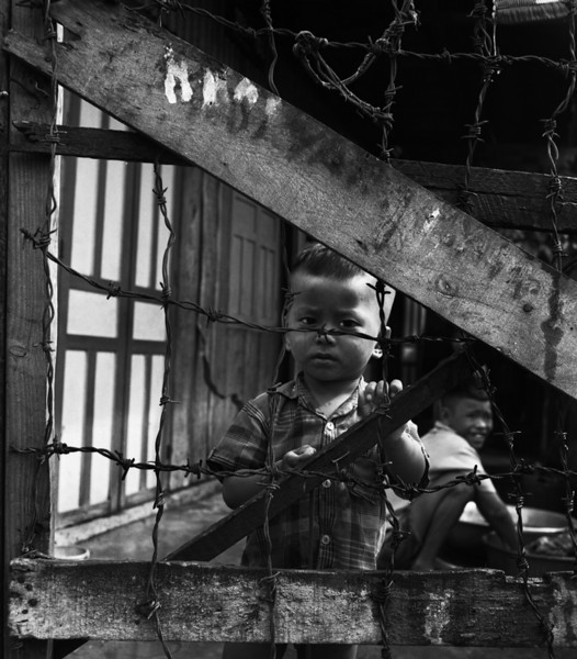 """On a walk through Na Trang, Vietnam, a boy cries. I drunkenly, stumble along with a camera singing Bette Midler's """"I think it's going to rain today."""" The boy stops crying and becomes what one editor would see as the era's barbed-wire icon. """"Era of Barbed Wire,"""" he would call what now frames my view. I see it too and sober up. """"Scarecrows dressed in the latest styles, """"the frozen smiles to chase love away,"""" I sing and walk on."""
