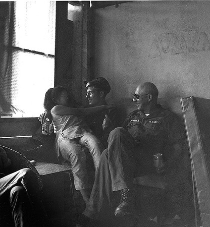 Navy Photographer Kent Van Hoesen is entertained by a local lady in a Na Trang bar. Commander John J. Jamroga, who would eventually retire to Washington and head a military photographer's organization,  is then the photo lab head officer. We call him Mr. J and he has taken his men to relax in the city.