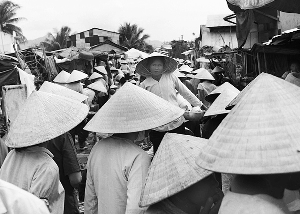 "The Na Trang crowd pushes me through a sea of hats. I tower over the ladies in the open-air market. Strangely something stops the world, and the woman in the center of the photograph looks my way. We recognize each other from another life. I'm deeply touched. When I click this image, the Earth moves again, as the crowd pushes on and closes our moment. I want to say something in a language I've either forgotten, or don't yet know. But it's too late. ""Tin can at my feet, think I'll kick it down the street,"" I tell her. ""That's the way to treat a friend."""