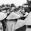 """The Na Trang crowd pushes me through a sea of hats. I tower over the ladies in the open-air market. Strangely something stops the world, and the woman in the center of the photograph looks my way. We recognize each other from another life. I'm deeply touched. When I click this image, the Earth moves again, as the crowd pushes on and closes our moment. I want to say something in a language I've either forgotten, or don't yet know. But it's too late. """"Tin can at my feet, think I'll kick it down the street,"""" I tell her. """"That's the way to treat a friend."""""""