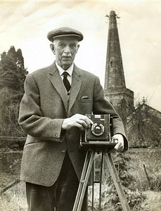 Robert H Bisco with his trusty Sanderson 1/2 plate Camera. In the background is Newent St Mary's Church with work being done on the spire 1971/72.