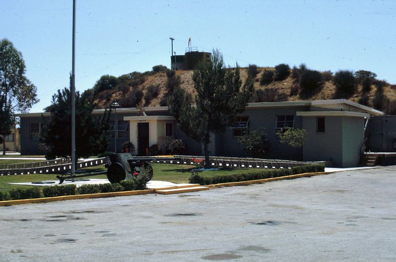 LA-78 Malibu Site - Admin Area - Mess Hall - WW2 Field Gun by Flag Pole - Aug 1966 <br /> In background on top of small hill is the water tank that provided water for Admin and Launching Areas.  Water was pumped up the mountain from Malibu Water Co.