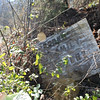 9. This Brooks cemetery sign is barely visible in the weeds at the base of the trail leading up to the grave.