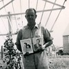 6g. Jim Walker holding photos, perhaps of his daughter Martha and her husband, and his son, Charles.