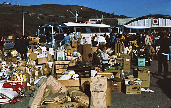 4*Mon, Jan 18, 1971<br /> People: Laurie sitting, crowd<br /> Subject: supplies<br /> Place: Mill Valley, Marin Co, Ca<br /> Activity: gathering supplies and people for taking charter  busses to Bolinas Lagoon to help clean-up oil spill<br /> Comments: I think it was a tanker off the Golden Gate.  That's my daughter in the center.  She still helps clean-ups.