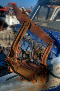 © Joseph Dougherty. All rights reserved.  A rusty hood spring on an old truck in a junkyard in Richmond, CA.