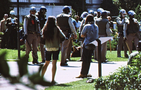 4*Wed, Apr 15, 1970 copy, severe crop<br /> *People: 10 cops<br /> Subject: student laying in grass<br /> *Place: UC campus<br /> Activity: protest ROTC<br /> Comments: defying the cops.  One cop is checking me out.   One cop is calling his supervisor. Reporter on left.