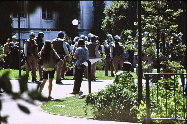 4*Wed, Apr 15, 1970 original<br /> *People: 10 cops<br /> Subject: student laying in grass<br /> *Place: UC campus<br /> Activity: protest ROTC<br /> Comments: defying the cops.  One cop is checking me out.   One cop is calling his supervisor. Reporter on left.