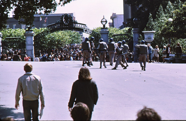 4*Wed, Apr 15, 1970<br /> *People: 8 cops<br /> Subject: clearing plaza<br /> *Place: Sather Gate<br /> Activity: protest<br /> Comments: cops getting pelted by junk thrown