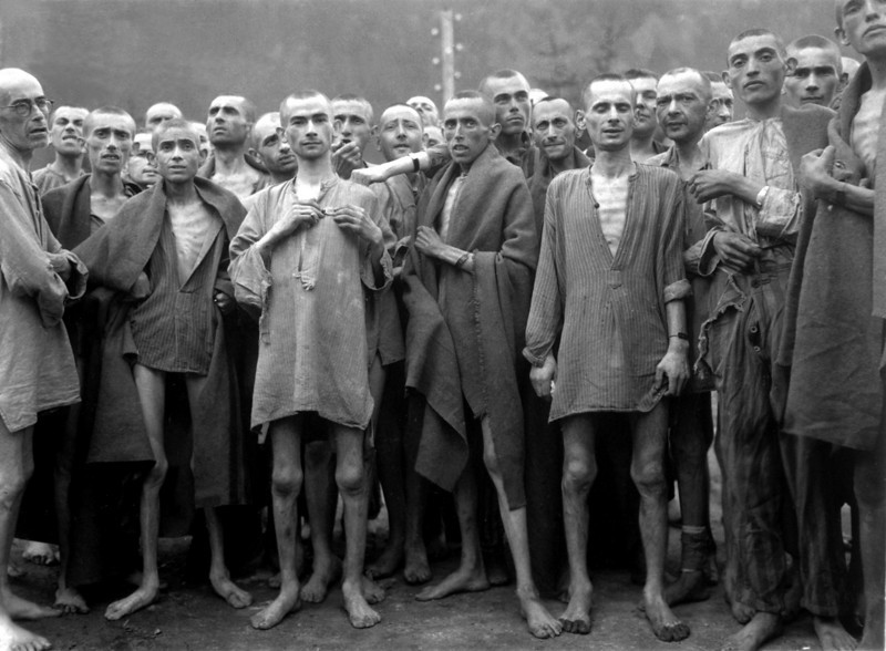 """Starved prisoners, nearly dead from hunger, pose in concentration camp in Ebensee, Austria.  The camp was reputedly used for """"scientific"""" experiments.  It was liberated by the 80th Division.  May 7, 1945.  Lt. A. E. Samuelson.  (Army)<br /> NARA FILE #:  111-SC-204480<br /> WAR & CONFLICT BOOK #:  1103"""