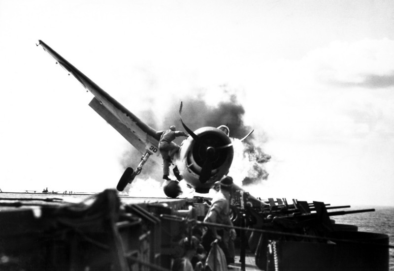 Crash landing of F6F on flight deck of USS ENTERPRISE while enroute to attack Makin Island.  Lt. Walter Chewning, catapult officer, clambering up the side of the plane to assist pilot, Ens. Byron Johnson, from the flaming cockpit.  November 1943.  (Navy)<br /> Exact Date Shot Unknown<br /> NARA FILE #:  080-G-205473<br /> WAR & CONFLICT BOOK #:  964