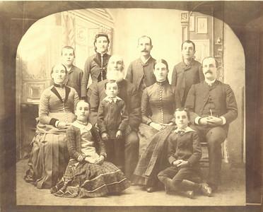 "John Quayle family, taken in Ishpeming, MI in about 1887. Rear row, L to R:  James (B: 3 NOV 1874, D: 17 NOV 1935) Mona (B: 1 NOV 1870, D: 25 APR 1966) John Jr. (B: 29 MAR 1864, D: 21 SEP 1929) William (B: 16 NOV 1872, D: 7 NOV 1939) Middle row, L to R: Margaret (Bridson) Quayle John Quayle Catherine (Quayle) Buzzo (""Aunt Kate"") (B: 8 APR 1867, D: 25 FEB 1920) Richard Quayle (""Uncle Dick"") (B: 21 JUL 1862, D: 6 JUL, 1934) Front row, L to R: Anna Margaret (Quayle) Kennaugh (""Aunt Annie"") (B: 17 AUG 1876, D: 20 MAR 1955) Thomas Quayle (B: 28 AUG 1882, D: 12 OCT 1890) Phillip Quayle (B: 15 AUG 1879, D: 18 NOV 1954)"