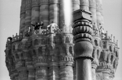 Iron pillar top in front, Qutub Minar in back