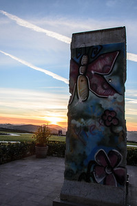 A real piece of the Berlin Wall contrasted with the beauty of a free world as represented by the golden sunset.