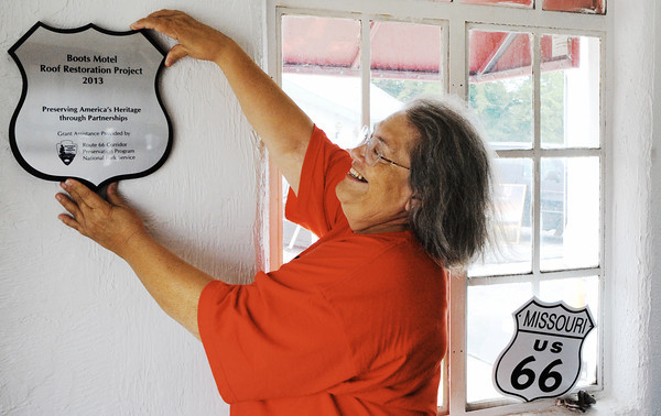 Globe/T. Rob Brown<br /> Debye Harvey, co-owner of Boots Court, looks for an appropriate location to hang a new plaque from the National Park Service Monday morning, July 29, 2013, inside the historic Route 66 Boots Motel location in Carthage.